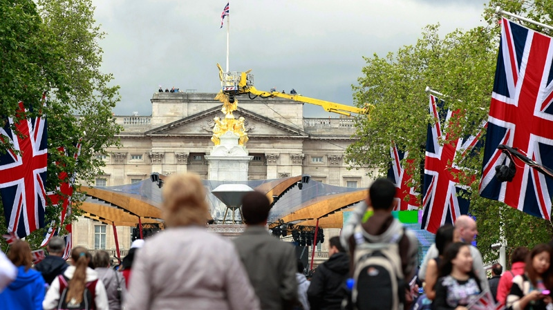 Members of the public make their way down the Mall to wait for the start of a pop music concert at Buckingham Palace, seen in background, to help celebrate Queen Elizabeth II's 60-year reign during Diamond Jubilee celebrations in London, Monday, June 4, 2012. (AP / Tim Hales)