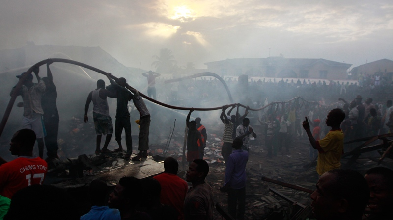 The local population join with rescue workers at the site of a plane crash in Lagos, Nigeria, in this photo dated Sunday, June 3, 2012.(AP / Sunday Alamba, file)