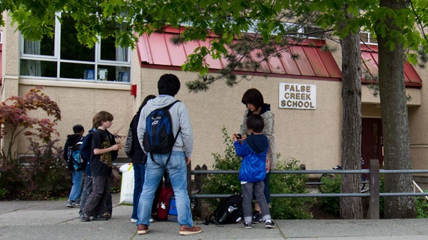 Parents and students gather at False Creek Elementary School after a human hand was delivered to the school earlier in the day in Vancouver, B.C., on Tuesday June 5, 2012. (Darryl Dyck / THE CANADIAN PRESS)