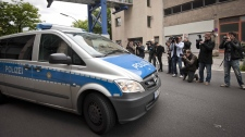 A police car leaves the central police detention facility of Berlin supposed to carry Luka Rocco Magnotta who is to be brought before a judge in Berlin, Germany, Tuesday, June 5, 2012.  (AP / Timur Emek)