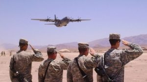 An Australian C130 takes off carrying the bodies of two Australian soldiers who were killed by an improvised explosive device in southern Afghanistan as members of the US Army 101st Aviation Group salute during take off in Tarin Kowt, Afghanistan on Wednesday, June 9, 2010. (AP / Jim St. Pierre)
