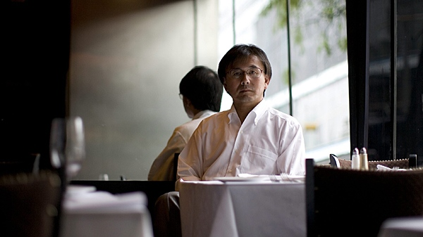 """Fred Luk, owner of the restaurant """"Fred's Not Here"""" sits at one of the tables at his Toronto eatery on Tuesday June 22, 2010. (THE CANADIAN PRESS/Chris Young)"""