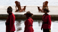 Four Royal Canadian Mounted Police walk the shore of Peninsula Lake as final preparations are made for the arrival of the leaders to the Muskoka 2010 G8 summit at the Deerhurst Resort in Huntsville, Ont., on Thursday June 24, 2010. (Sean Kilpatrick / THE CANADIAN PRESS)