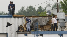 Workers clear away debris from the roof of a building in the town of Midland, Ont., Thursday, June 24, 2010, following a tornado which left a number of injuries and damage to property and businesses in its wake. (Graham Hughes / THE CANADIAN PRESS)
