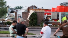 People look at a damaged building after a severe storm in Midland, Ontario, Wednesday June 23, 2010. (Benjamin Ricetto / THE CANADIAN PRESS)