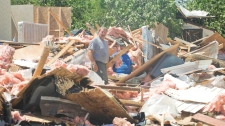 Al MacDonald, left, and Lloyd Scott look through the remains of Mr. Scott's trailer home at Smiths' trailer park and camp in the town of Midland, Ontario, Thursday, June 24, 2010. (Graham Hughes / THE CANADIAN PRESS)