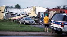 A car sits in front of a damaged building after a severe storm in Midland, Ontario, Wednesday, June 23, 2010. (Benjamin Ricetto / THE CANADIAN PRESS)