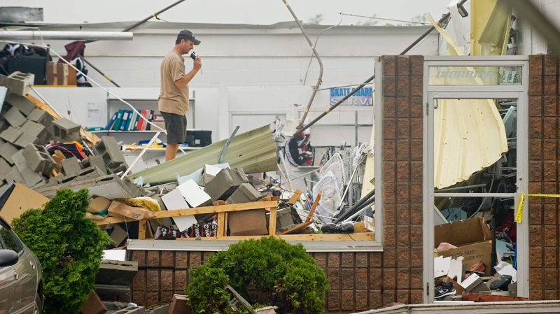 A man survey's the damage done to a building in the town of Midland, Ontario, Thursday, June 24, 2010, following a tornado which left a number of injuries and damage to property and businesses in its wake. (Graham Hughes / THE CANADIAN PRESS)