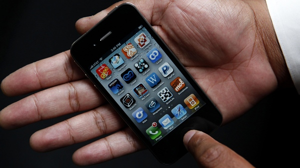 An Associated Press reporter holds the new Apple iPhone during a product test review in San Francisco, Thursday, June 24, 2010. (AP / Jeff Chiu)