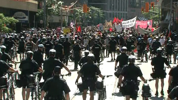 Police keep an eye on approximately 1,000 protesters making their way along College Street from Allan Gardens in  Toronto, Friday, June 25, 2010.