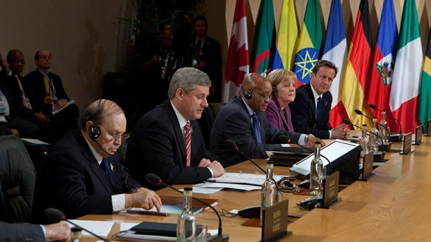 Canada's Prime Minister Stephen Harper, second from left, makes an announcement with, from left, Algerian President Abdelaziz Bouteflika, South African President Jacob Gedleyihlekisa Zuma, German Chancellor Angela Merkel and United Kingdom Prime Minster David Cameron at the Outreach country leader's working session at the G8 Summit in Huntsville, Ont. on Friday, June 25, 2010. (G-8/G20 Host Photo/Peter Bregg)