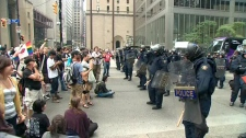 Riot police keep a close eye on a large crowd gathered at King and Bay streets, Sunday evening, June 27, 2010.