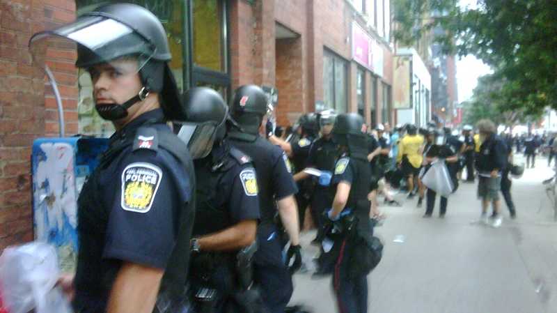 Detained people that were removed from the crowd are lined up at Queen and Spadina in downtown Toronto, Sunday night, June 27, 2010. (Lisa LaFlamme / CTV News)