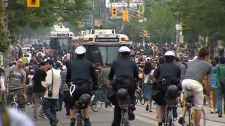 Police follow a large crowd moving west along Queen Street in downtown Toronto, Sunday evening, June 27, 2010.