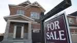A new house with a for sale sign is shown in this undated file photo. (Sean Kilpatrick / The Canadian Press)