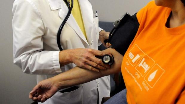 A nurse practitioner checks blood pressure