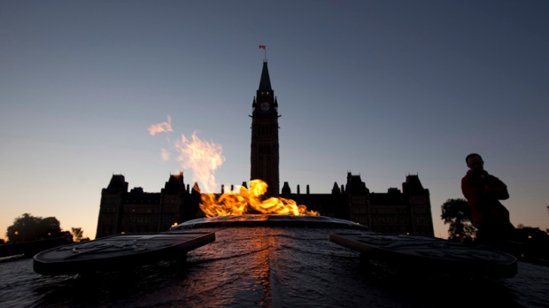 Visitors come and go as the Parliament Buildings are silhouetted at dusk in Ottawa on June 13, 2012. (Adrian Wyld/THE CANADIAN PRESS)