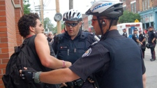 Anti-G20 protester Dionysos Savopoulos is detained by police on Sunday afternoon in Toronto, after spending the night in a temporary detention facility, Sunday, June 27, 2010.