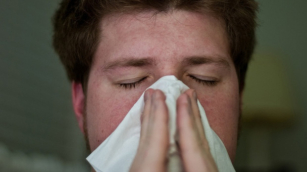 Man blows his nose from common cold