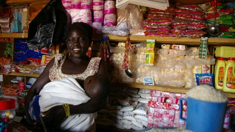 Akot Florence, 22, and her baby in the convenience store she runs in Kalongo, Uganda. Akot says people used to rip her off before she learned how to read and write in a mothers group. (Darcy Wintonyk/ CTV)