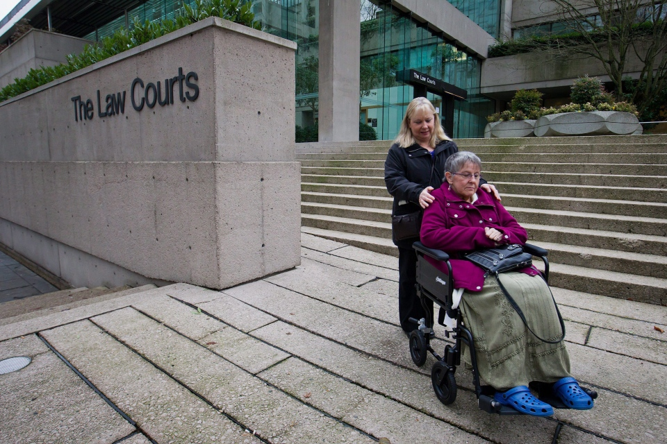 Gloria Taylor, right, is assisted by her sister Patty Ferguson as they pause for media outside British Columbia Supreme Court in this December 2011. Taylor has since passed away, but her fight for doctor-assisted suicide continues. (Darryl Dyck /THE CANADIAN PRESS)