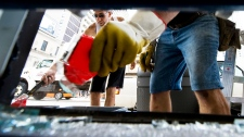 Workers remove broken glass at a store on Yonge Street after the weekend's anti-G20 protests in Toronto, on Monday, June 28, 2010. (Adrien Veczan / THE CANADIAN PRESS)