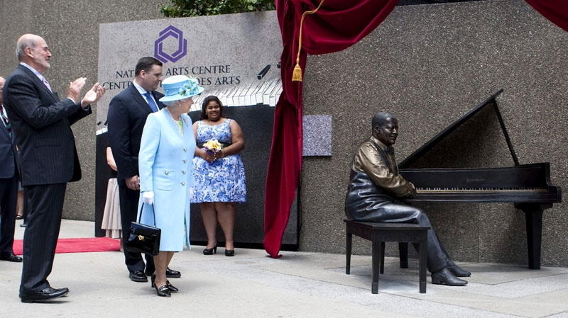 Queen Elizabeth takes part in the unveiling of a statue of Canadian jazz legend Oscar Peterson in Ottawa on June 30, 2010. Oscar Peterson's daughter Celine looks on at back. (Sean Kilpatrick / THE CANADIAN PRESS)