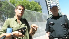 Charlie Veitchm, left, is seen speaking with a police officer in front of the G-20 summit security fence in Toronto. The 29-year-old filmmaker, was arrested Tuesday as he was about to board a plane at Toronto airport and charged of impersonating an officer.