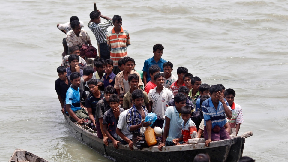 Rohingya Muslims, fleeing from ethnic violence in Myanmar between Buddhists and minority Rohingya Muslims, are brought by Bangladeshi border guards to a boat jetty at Shahporir Dwip in Taknaf, Bangladesh, Monday, June 18, 2012. (AP Photo/ Saurabh Das)