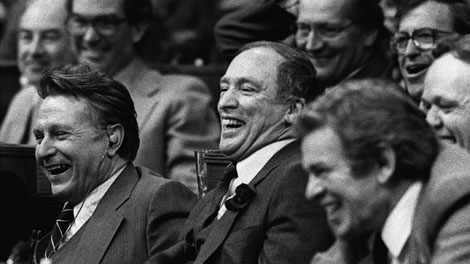 Prime Minister Pierre Trudeau, centre, shares a laugh with fellow Liberal MPs Allan MacEachen (then the deputy prime minister), left, and John Munro, right, during voting on amendments to the constitution in the House of Commons, Ottawa, April 23, 1981. (CP Photo/Andy Clark)