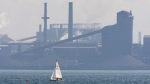 A sailing boat sails past the Stelco plant in Hamilton, Ont. in this Aug. 27, 2007, before its purchase by US Steel. (Adrian Wyld / THE CANADIAN PRESS)