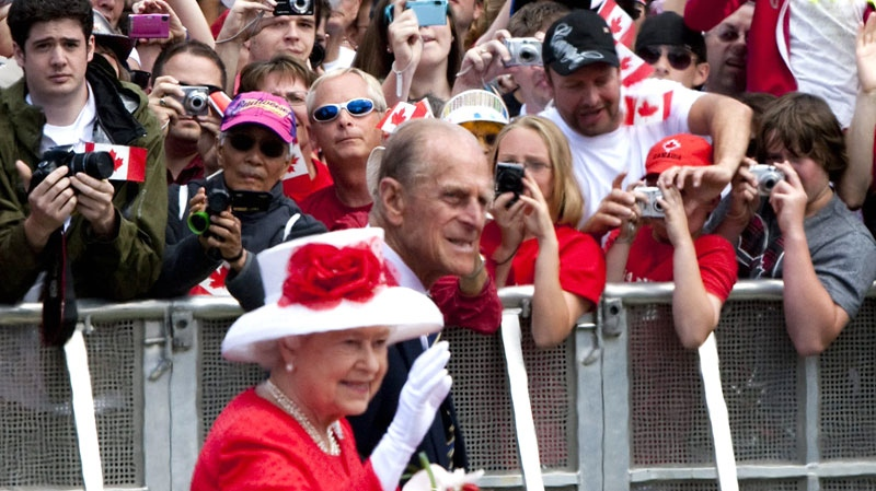 Crowds work to snap a glimpse of Queen Elizabeth II and Prince Philip during Canada Day celebrations on Parliament Hill in Ottawa on July 1, 2010. The royal couple is on a nine-day tour of Canada. (Sean Kilpatrick / THE CANADIAN PRESS)