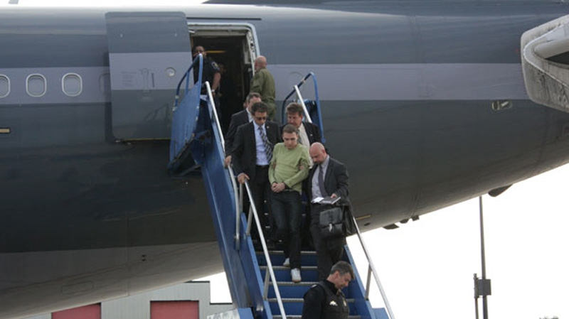 Luka Rocco Magnotta descends the stairs of an airplane flanked by Montreal police on June 18, 2012. (Montreal Police)