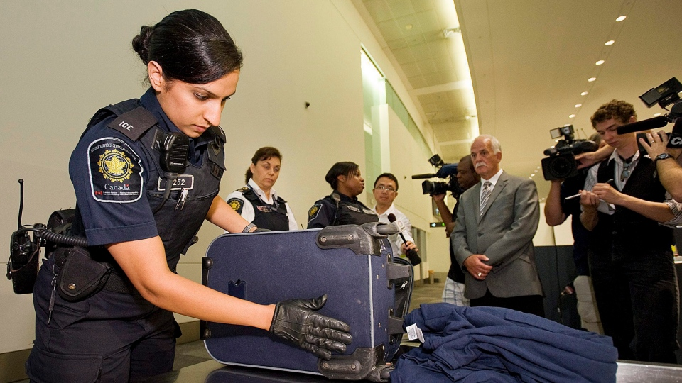 CBSA officer Nav Rogers inspects a piece of luggage while media and Public Safety Minister Vic Toews, right centre, looks on during a demonstration of a typical secondary examination involving travellers arriving from abroad by the Canadian Boarder Services Agency at Pearson Airport in Toronto on Tuesday, August 9, 2011.