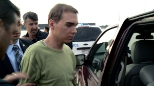 Luka Rocco Magnotta is taken by police from a Canadian military plane to a waiting van in Mirabel, Que., on Monday, June 18, 2012.