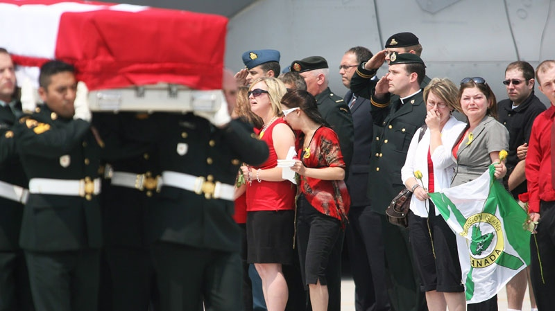 Grieving family members watch as the flag-draped casket of Sergeant James Patrick MacNeil is carried by the military bearer party to a waiting hearse during a repatriation ceremony at CFB Trenton on June 25, 2010. (Peter Redman / THE CANADIAN PRESS)