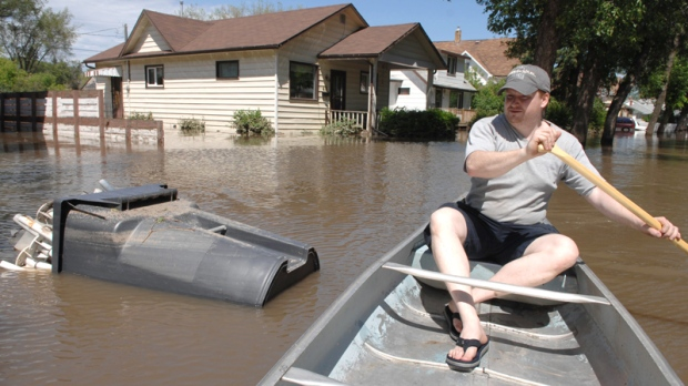 Mark Lints rows down Agricultural Street following a torrential downpour that caused flooding in Yorkton, Saskatchewan on Friday, July 2, 2010. (Mark Taylor /  THE CANADIAN PRESS)