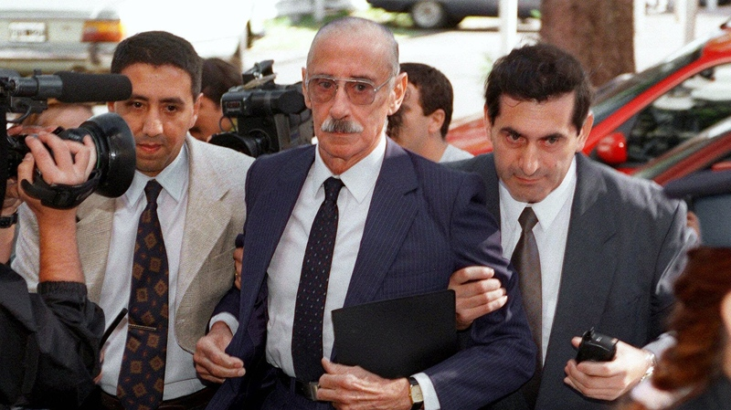 Former Argentine military President Jorge Rafael Videla, center, escorted by plain clothes police officers, arrives at a Buenos Aires Federal Court Friday, Feb. 18, 2000.  (AP / Sergio Llamera/La Nacion)