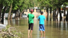 Two boys survey the flooding on Agricultural Street in Yorkton, Saskatchewan on Friday, July 2, 2010. (Mark Taylor / THE CANADIAN PRESS)