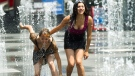 People cool down in the water sprinklers at Dundas Square as they take in the extreme heat in Toronto on Tuesday, June 19, 2012. (Nathan Denette/THE CANADIAN PRESS)
