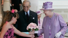 Queen Elizabeth accepts flowers from Caledon Lamb and Kirsten Benidickson as Arthur Mauro, chair of the Winnipeg Airports Authority looks on at the new terminal at James Richardson International Airport in Winnipeg, Saturday, July 3, 2010. (John Woods / THE CANADIAN PRESS)