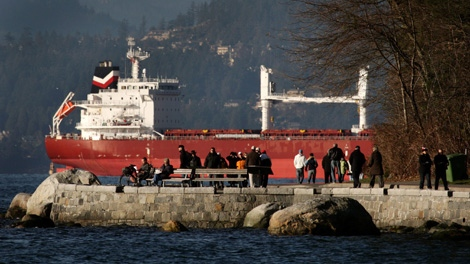 People walk along the Stanley Park Seawall as a cargo ship waiting to enter port sits anchored at the mouth of Burrard Inlet in Vancouver, B.C., on Sunday December 27, 2009. (CP/Darryl Dyck)