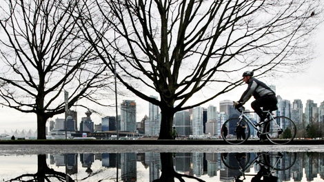 A man is reflected in a puddle of water as he rides a bike through Stanley Park in Vancouver, B.C., on Sunday January 3, 2010. (CP/Darryl Dyck)