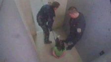 This image taken from surveillance video shows a guard holding Willow Kinloch against the back wall of a holding cell.