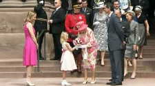 Queen Elizabeth II receives flowers from a young girl on the steps of Queen's Park in Toronto on Tuesday, July 6, 2010.