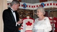 Queen Elizabeth II and Prime Minister Stephen Harper chat after the Queen unveiled a hockey display in her honour at a state dinner in Toronto on Monday July 5, 2010. (Frank Gunn / THE CANADIAN PRESS(