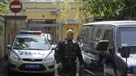 A traffic police car guards an entrance, as an armored vehicle and a riot police officer in a heavy gear leave the Lefortovo prison in Moscow, Thursday, July 8, 2010. (AP Photo/Misha Japaridze)