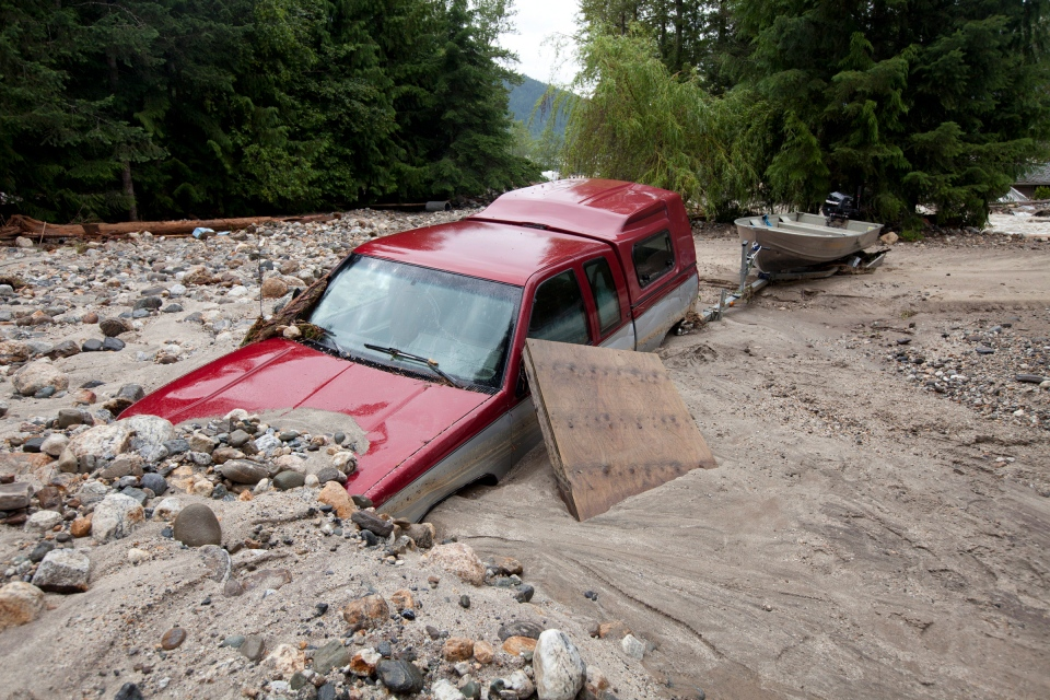 A truck is buried in sediment in Two Mile just outside of Sicamous, B.C. Monday, June 25, 2012.  (Jonathan Hayward / THE CANADIAN PRESS)