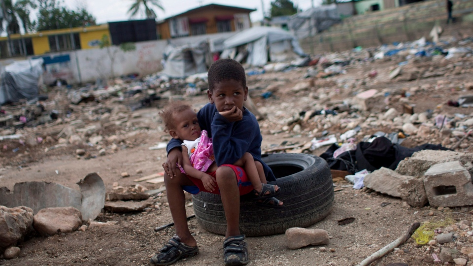 Six-year-old Charles Kerby hold his 11-month-old sister Mikerlina Dragon inside the Ste Therese camp, set up for people displaced by the 2010 earthquake, in Petion-Ville, Haiti,  on Saturday, June 16, 2012. (AP / Dieu Nalio Chery)