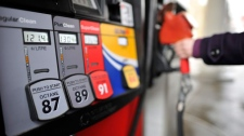 A motorist reaches for the pump at a gas station in Toronto on Thursday, Feb. 24, 2011. (The Canadian Press/Patrick Dell)